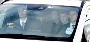 Jurgen Klopp (centre) is escorted away after arriving at John Lennon Airport, Liverpool. Photo: Peter Byrne/PA