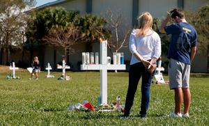 Mourners look at a memorial for the victims of the Marjory Stoneman Douglas High School shooting, in a park in Parkland, Florida on February 16, 2018.  A former student, Nikolas Cruz, opened fire at the Florida high school leaving 17 people dead and 15 injured. / AFP PHOTO / RHONA WISERHONA WISE/AFP/Getty Images