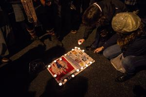 BARCELONA, SPAIN - JANUARY 07:  People light candles on a Charlie Hebdo Magazine during a gathering of people showing their support for the victims of the terrorist attack at French magazine Charlie Hebdo, in front of the Consulate of France on January 7, 2015 in Barcelona, Spain. Twelve people were killed, including two police officers, as two gunmen opened fire at the magazine offices of Charlie Hebdo in Paris, France.   (Photo by David Ramos/Getty Images)