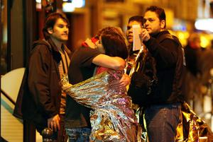 People hug each other before being evacuated by bus, near the Bataclan concert hall in central Paris, on November 14, 2015. More than 100 people were killed in a mass hostage-taking at a Paris concert hall on November 13 and many more were feared dead in a series of bombings and shootings, as France declared a national state of emergency.      AFP PHOTO / FRANCOIS GUILLOTFRANCOIS GUILLOT/AFP/Getty Images