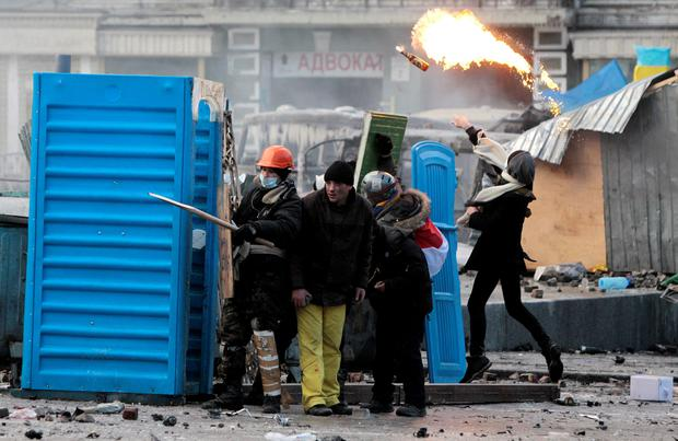 Protesters clash with police, in central Kiev, Ukraine, Monday, Jan. 20, 2014. Protesters erected barricades from charred vehicles and other materials in central Kiev as the sound of stun grenades can be heard in the freezing air as police try to quell anti-government street protests.  (AP Photo/Sergei Chuzavkov)