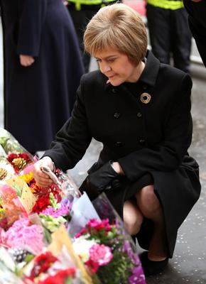 Scotland's First Minister Nicola Sturgeon views flowers left near to the scene of yesterday's bin lorry crash in Glasgow. PRESS ASSOCIATION Photo. Picture date: Tuesday December 23, 2014. See PA story POLICE Lorry. Photo credit should read: Andrew Milligan/PA Wire