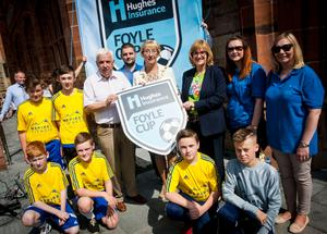 The Mayor of Derry City and Strabane District Council, Alderman Hilary McClintock pictured with Michael Hutton, organiser, Hughes Insurance Foyle Cup and Kim Hetherington, Acting Branch Manager, Hughes Insurance, Derry. Included are Hughes Insurance Foyle Cup representatives an some young local footballers who will take part in this year's tournament.