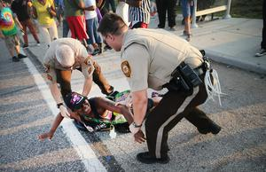 A demonstrator is arrested while protesting the killing of teenager Michael Brown on August 19, 2014 in Ferguson, Missouri.   (Photo by Scott Olson/Getty Images)