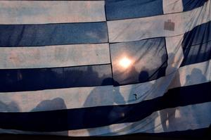 Protesters stand behind a huge greek flag in front of the greek parliament in central Athens, on June 29, 2015.  Some 17,000 people took to the streets of Athens and Thessalonique to say 'No' to the latest offer of a bailout deal Monday, accusing Greece's international creditors of blackmail. AFP PHOTO / LOUISA GOULIAMAKILOUISA GOULIAMAKI/AFP/Getty Images