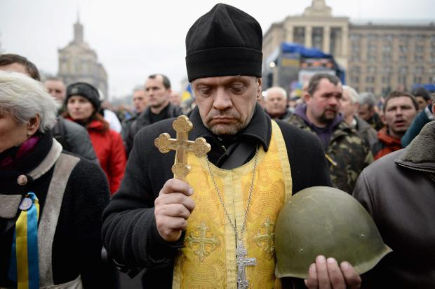 KIEV, UKRAINE - FEBRUARY 22:  A priest holds the helmet of an anti-government demonstrator killed in clashes with police before it is layed on display in Independence square February 22, 2014 in Kiev, Ukraine. The offices of Ukrainian President Viktor Yanukovych have been left unguarded, with the protesters in full control of the streets surrounding the government district. The opposition have called for elections to take place on May 25 and demanded that President Yanukovych stand down immediately. (Photo by Jeff J Mitchell/Getty Images)