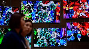 Visitors walk past a display made up of Samsung SUHD TV screens at the booth of South Korean electronics giant Samsung ahead of the opening of the 55th IFA (Internationale Funkausstellung) electronics trade fair in Berlin on September 3, 2015. IFA, Europe's largest consumer electronics and home appliances fair opens from September 4 to September 9, 2015. AFP PHOTO / JOHN MACDOUGALLJOHN MACDOUGALL/AFP/Getty Images