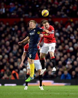 Southampton's James Ward-Prowse (left) and Manchester United's Wayne Rooney battle for the ball in the air during the Barclays Premier League match at Old Trafford, Manchester. Martin Rickett/PA Wire.
