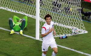 Russia's goalkeeper Igor Akinfeev, left, lies in the goal as South Korea's Koo Ja-cheol celebrates after scoring the opening goal during their group H World Cup soccer match at the Arena Pantanal in Cuiaba, Brazil, Tuesday, June 17, 2014. (AP Photo/Thanassis Stavrakis)