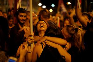 Supporters of the No vote react after the  results of the referendum at Syntagma square in Athens, Sunday, July 5, 2015. Greece faced an uncharted future as its interior ministry predicted Sunday that more than 60 percent of voters in a hastily called referendum had rejected creditors' demands for more austerity in exchange for rescue loans. (AP Photo/Emilio Morenatti)