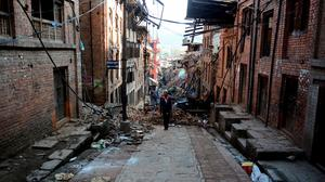 "A man walks amidst the rubble of collapsed houses in Bhaktapur, on the outskirts of Kathmandu, on April 27, 2015, two days after a 7.8 magnitude earthquake hit Nepal. Nepalis started fleeing their devastated capital on April 27 after an earthquake killed more than 3,800 people and toppled entire streets, as the United Nations prepared a ""massive"" aid operation.  AFP PHOTO / PRAKASH MATHEMAPRAKASH MATHEMA/AFP/Getty Images"