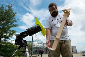 "Kwayera Davis shows a solar eclipse viewer next to a telescope which he is seeing up in Charleston, South Carolina, on the day of the total solar eclipse, on August 21, 2017. The Sun started to vanish behind the Moon as the partial phase of the so-called Great American Eclipse began Monday, with millions of eager sky-gazers soon to witness ""totality"" across the nation for the first time in nearly a century. / AFP PHOTO / MANDEL NGANMANDEL NGAN/AFP/Getty Images"