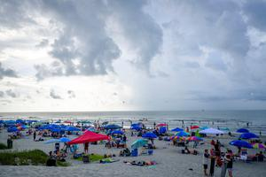 "ISLE OF PALMS, SC - AUGUST 21:  Solar eclipse watchers on the beach hoping to view the total solar eclipse if the weather clears on August 21, 2017 in Isle of Palms, South Carolina. It's been 99 years since a total solar eclipse crossed the country from the Pacific to the Atlantic. Millions of people have flocked to areas of the U.S. that are in the ""path of totality"" in order to experience a total solar eclipse. During the event, the moon will pass in between the sun and the Earth, appearing to block the sun. Isle of Palms is one of last vantage points where totality will be visible. (Photo by Pete Marovich/Getty Images)"