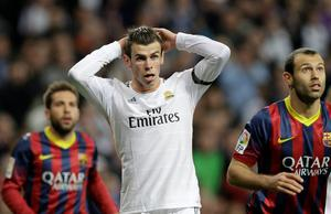 Real Madrid's Gareth Bale, centre reacts,  during a Spanish La Liga soccer match against FC Barcelona at the Santiago Bernabeu stadium in Madrid, Sunday March 23, 2014. (AP Photo/Paul White)