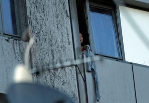 A person peers out of a window from a building on fire in London, Wednesday, June 14, 2017. Metropolitan Police in London say they're continuing to evacuate people from a massive apartment fire in west London. The fire has been burning for more than three hours and stretches from the second to the 27th floor of the building.(AP Photo/Matt Dunham)