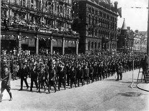Crowds in Belfast line the streets as soldiers returning from the Great War march past Belfast City Hall.