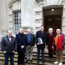 Campaigners for a Police Ombudsman investigation into a UVF gun attack on the Thierafurth Inn Pub in Kilcoo, Co Down at Belfast High Court. Included are South Down MP Chris Hazzard (second left) and solicitor Gavin Booth (third right).