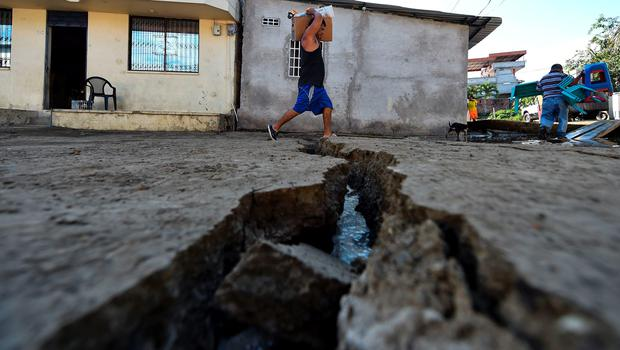 A man evacuates his belongings in Manta, Ecuador, on April 17, 2016 a day after a powerful 7.8-magnitude quake hit the country. The toll from the big earthquake in Ecuador rose on Sunday to 246 dead and 2,527 people injured, the country's vice president said. / AFP PHOTO / LUIS ACOSTALUIS ACOSTA/AFP/Getty Images