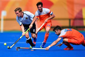 Germany's Mats Grambusch (L) is tackled by Netherlands' Robbert Kemperman during the mens's field hockey Germany vs Netherlands match of the Rio 2016 Olympics Games at the Olympic Hockey Centre in Rio de Janeiro on August, 12 2016. / AFP PHOTO / MANAN VATSYAYANAMANAN VATSYAYANA/AFP/Getty Images