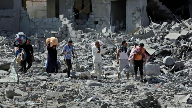 Palestinians carry their belongings through rubble of houses destroyed by Israeli strikes, as they visit the area during a 12-hour cease-fire in Beit Hanoun, northern Gaza Strip, Saturday, July 26, 2014 (AP Photo/Lefteris Pitarakis)