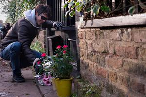 A man leaves flowers outside George Michael's London home, as the pop superstar has died at the age of 53 from suspected heart failure.
