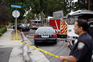 SANTA MONICA, CA - JUNE 07:  A police officer holds police line tape at the scene of a bullet-riddled crashed car in which a woman was reportedly shot, near a burning home with two bodies inside, after multiple shootings were reported at various locations including Santa Monica College June 7, 2013 in Santa Monica, California. According to reports, at least six people have been injured, and a suspect was taken into custody.  (Photo by David McNew/Getty Images)