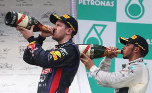 KUALA LUMPUR, MALAYSIA - MARCH 24:  Race winner Sebastian Vettel (L) of Germany and third placed Lewis Hamilton (R) of Great Britain and Mercedes GP celebrate on the podium following the Malaysian Formula One Grand Prix at the Sepang Circuit on March 24, 2013 in Kuala Lumpur, Malaysia.  (Photo by Mark Thompson/Getty Images)