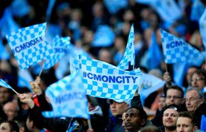 Manchester City fans wave flags in the stands during the UEFA Champions League Quarter Final, Second Leg match at the Etihad Stadium, Manchester. Nigel French/PA Wire