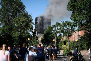 LONDON, ENGLAND - JUNE 14:  People watch as smoke rises from the building after a huge fire engulfed the 24 story Grenfell Tower in Latimer Road, West London in the early hours of this morning on June 14, 2017 in London, England.  The Mayor of London, Sadiq Khan, has declared the fire a major incident as more than 200 firefighters are still tackling the blaze while at least 30 people are receiving hospital treatment.  (Photo by Carl Court/Getty Images)