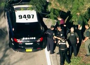 In this frame grab from video provided by WPLG-TV, law enforcement personnel arrest an unidentified man (in dark red), following a shooting at Marjory Stoneman Douglas High School in Parkland, Fla., Wednesday, Feb. 14, 2018. A former student opened fire at the Florida high school Wednesday, killing more than a dozen people and sending scores of students fleeing into the streets. (WPLG-TV via AP)