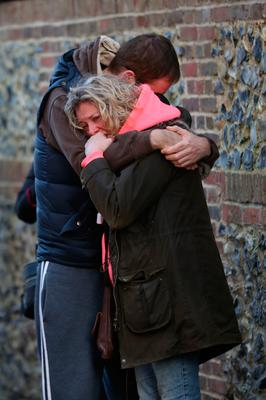 A woman is hugged as she weeps outside the Oxfordshire home of George Michael