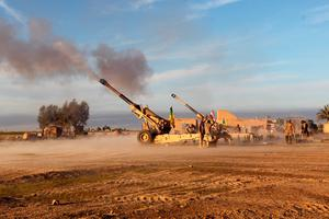 Iraqi Shiite fighters, members of Iraq's Popular Mobilisation units backing the government, fire Howitzer Cannons towards Isis positions on March 7, 2015, on the outskirts of the Iraqi town of Ad-Dawr during a military operation to retake the Tikrit area. Iraqi forces faced tough resistance from jihadist fighters around Tikrit, but the top US military officer said ahead of a Baghdad visit that victory was only a matter of time. AFP/Getty Images