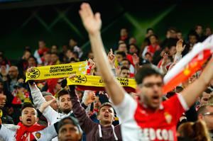 Monaco supporters with Borussia banners react in the stadium after the match was postponed amid an explosion near the bus of Borussia Dortmund some 10km away from the stadium prior to the UEFA Champions League 1st leg quarter-final football match BVB Borussia Dortmund v Monaco in Dortmund, western Germany on April 11, 2017. / AFP PHOTO / Odd ANDERSENODD ANDERSEN/AFP/Getty Images