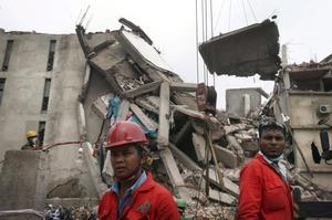 Workers watch as a crane lowers the ceiling of the garment factory building which collapsed in Savar, near Dhaka, Bangladesh on Monday April 29, 2013. Rescue workers in Bangladesh gave up hopes of finding any more survivors in the remains of a building that collapsed five days ago, and began using heavy machinery on Monday to dislodge the rubble and look for bodies - mostly of workers in garment factories there. At least 381 people were killed when the illegally constructed, 8-story Rana Plaza collapsed in a heap on Wednesday morning along with thousands of workers in the five garment factories in the building.(AP Photo/Wong Maye-E)