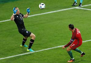 Portugal's Cristiano Ronaldo, right, takes a shot next to Iceland's goalkeeper Hannes Halldorsson, left, during the Euro 2016 Group F soccer match between Portugal and Iceland at the Geoffroy Guichard stadium in Saint-Etienne, France, Tuesday, June 14, 2016. (AP Photo/Michael Sohn)