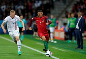 Portugal's Cristiano Ronaldo runs with the ball followed by Iceland's Kolbeinn Sigthorsson, left, and watched by Portugal coach Fernando Santos, right, during the Euro 2016 Group F soccer match between Portugal and Iceland at the Geoffroy Guichard stadium in Saint-Etienne, France, Tuesday, June 14, 2016. (AP Photo/Pavel Golovkin)
