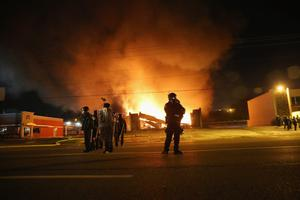 FERGUSON, MO - NOVEMBER 24:  Police officers watch as a business burns after it was set on fire during rioting following the grand jury announcement in the Michael Brown case on November 24, 2014 in Ferguson, Missouri. Ferguson has been struggling to return to normal after Brown, an 18-year-old black man, was killed by Darren Wilson, a white Ferguson police officer, on August 9. His death has sparked months of sometimes violent protests in Ferguson. A grand jury today declined to indict officer Wilson.  (Photo by Scott Olson/Getty Images)