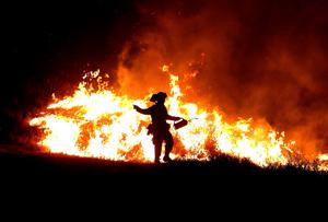 CLEARLAKE, CA - AUGUST 03:  A Cal Fire firefighter uses a drip torch to start a backfire as he battles the Rocky Fire on August 3, 2015 near Clearlake, California. Nearly 3,000 firefighters are battling the Rocky Fire that has burned over 60,000 acres has forced the evacuation of 12,000 residents in Lake County. The fire is currently 12 percent contained and has destroyed at least 14 homes. 6,300 homes are threatened by the fast moving  blaze.  (Photo by Justin Sullivan/Getty Images)