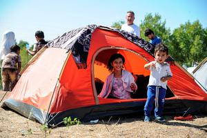 EDIRNE, TURKEY - SEPTEMBER 16: (TURKEY OUT) Syrian migrant children rest in a tent during their walk towards the Greece border on a road near Edirne, September 16, 2015 in Turkey. Since the beginning of 2015 the number of migrants using the so-called 'Balkans route' has exploded with migrants arriving in Greece from Turkey and then travelling on through Macedonia and Serbia before entering the EU via Hungary. The number of people leaving their homes in war torn countries such as Syria, marks the largest migration of people since World War II. (Photo by Gokhan Tan/Getty Images)