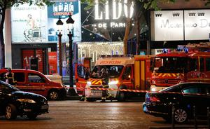 Firefighters and rescuers stand by the site of a shooting on the Champs Elysees in Paris on April 20, 2017. One police officer was killed and another wounded today in a shooting on Paris's Champs Elysees, police said just days ahead of France's presidential election. France's interior ministry said the attacker was killed in the incident on the world famous boulevard that is popular with tourists.  / AFP PHOTO / THOMAS SAMSONTHOMAS SAMSON/AFP/Getty Images