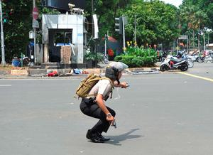 A police officer holds his pistol during a gun-battle with attackers near the site of an explosion, rear, in Jakarta, Indonesia Thursday, Jan. 14, 2016. Attackers set off explosions at a Starbucks cafe in a bustling shopping area in Indonesia's capital and waged gunbattles with police Thursday, leaving bodies in the streets as office workers watched in terror from high-rise windows. (AP Photo)