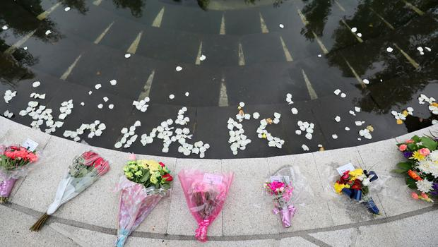 White Rose petals are thrown into a pond at the Omagh Memorial garden by people who attended the ceremony for victims of the car bomb on Market Street on the 15th August 1998. PRESS ASSOCIATION Photo. Picture date: Wednesday August 15, 2018. The worst single atrocity of the Northern Ireland conflict killed 29 people, including a woman pregnant with twins. See PA story ULSTER Omagh. Photo credit should read: Niall Carson/PA Wire