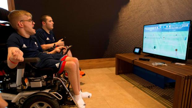 Patrick Wilson (L) and Jamie McCowan representing Great Britain in boccia play a video game in the Paralympic Village during the Paralympic Games in Rio de Janeiro, Brazil, on September 6, 2016. Photo by: Al Tielemans /OIS/IOC via AFP.  RESTRICTED TO EDITORIAL USE. / AFP PHOTO / OIS/IOC / Al Tielemans for OIS/IOCAL TIELEMANS FOR OIS/IOC/AFP/Getty Images