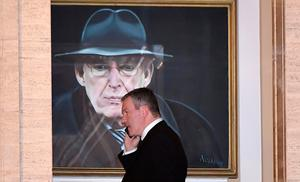 Conor Murphy, who has been considered as a possible replacement for Martin McGuinness' following his resignation today as Northern Ireland Deputy First Minister, talks on his phone as he walks past a painting of the late Ian Paisley at Stormont on January 9, 2017 in Belfast, Northern Ireland. (Photo by Charles McQuillan/Getty Images)