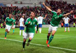Northern Ireland  midfielder Steven Davis (C) celebrates with Northern Ireland's defender Gareth McAuley (R) after scoring his team's third goal during the UEFA Euro 2016 qualifying Group F football match between Northern Ireland and Greece at Windsor Park in Belfast, Northern Ireland, on October 8, 2015.    AFP PHOTO / PAUL FAITHPAUL FAITH/AFP/Getty Images