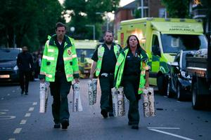 """Paramedics arrive with oxygen as a huge fire engulfs the Grenfell Tower early June 14, 2017 in west London.  The massive fire ripped through a 27-storey apartment block in west London in the early hours of Wednesday, trapping residents inside as 200 firefighters battled the blaze. Police and fire services attempted to evacuate the concrete block and said """"a number of people are being treated for a range of injuries"""", including at least two for smoke inhalation.   / AFP PHOTO / Daniel Leal-OlivasDANIEL LEAL-OLIVAS/AFP/Getty Images"""