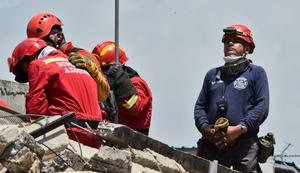 Peruvian rescuers pray as they search for survivors in Manta, in the Ecuadorean coastal province of Manabi, on April 18, 2016 two days after a 7.8-magnitude quake hit the country. Rescuers and desperate families clawed through the rubble Monday to pull out survivors of an earthquake that killed 350 people and destroyed towns in a tourist area of Ecuador. / AFP PHOTO / LUIS ACOSTALUIS ACOSTA/AFP/Getty Images