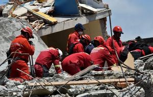 Peruvian rescuers search for survivors in Manta, in the Ecuadorean coastal province of Manabi, on April 18, 2016 two days after a 7.8-magnitude quake hit the country. Rescuers and desperate families clawed through the rubble Monday to pull out survivors of an earthquake that killed 350 people and destroyed towns in a tourist area of Ecuador. / AFP PHOTO / LUIS ACOSTALUIS ACOSTA/AFP/Getty Images
