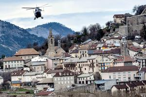 A helicopter of the French gendarmerie flies over Seyne-les-Alpes on March 28, 2015, near the site where a Germanwings flight crashed in the French Alps, killing all 150 aboard.