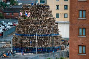 Loyalists sit on the Sandy Row bonfire being built in preparation for the 11th night bonfire on July 10, 2017 in Belfast.  (Photo by Jeff J Mitchell/Getty Images)